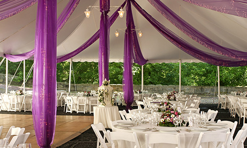 A fun, festive reception area with elegant floral centerpieces and purple details back-lit by twinkle lights.