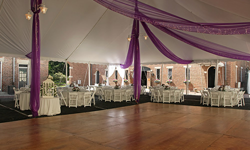 This large dance floor is laid with wood flooring and accented with white tables and purple decorations.