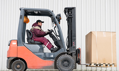 A member of the drayage crew moves pallets of materials.
