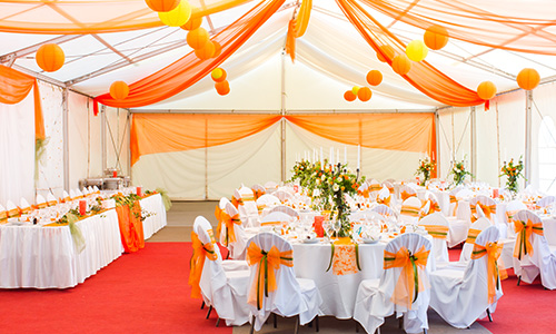A banquet room is decorated in white and shades of orange and yellow.