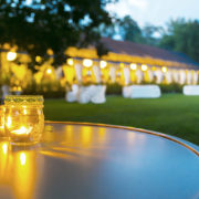 A large and beautifully lit outdoor tent for a wedding is pictured.