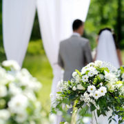 A beautiful flower arrangement is shown in the foreground while a couple getting married are shown in the background.