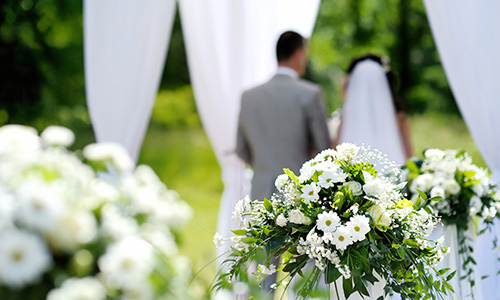 A bride and groom stand, surrounded by delicate white flowers and white fabric.