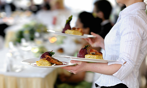 A server carries plates of gourmet food to tables.