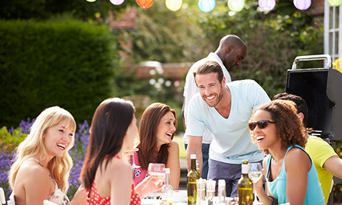 A group of young professionals chat and laugh around a picnic table.