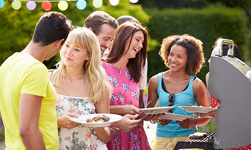 A group of young professionals gather and talk at a company picnic.