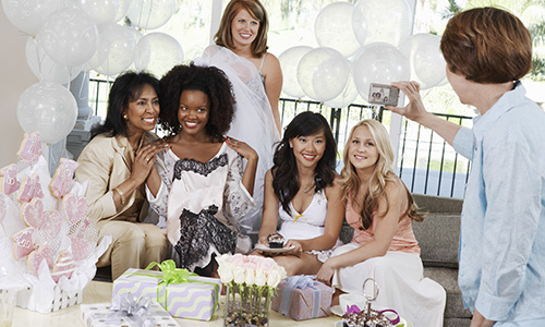 Women gather together for an elegant bridal shower decorated with balloons and flowers.