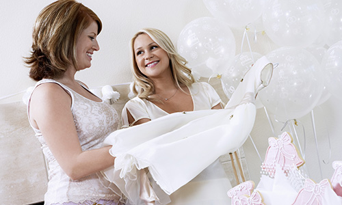 Two women look at flower girl dresses at a lovely pink and white bridal shower.