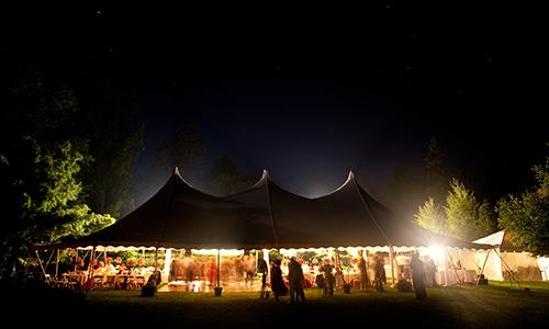 An open tent's dance floor is warmly lit by simple lighting.