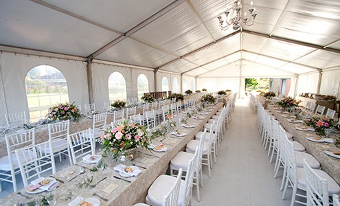 A long tent filled with elegantly set banquet tables on sophisticated hard flooring.