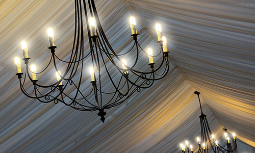A billowing tent liner with delicate black chandeliers create an elegant scene.