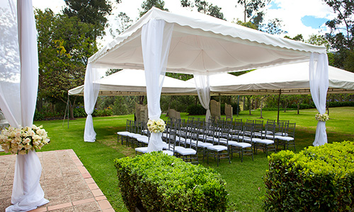 A tall open tent provides shades for outdoor seating for this wedding.