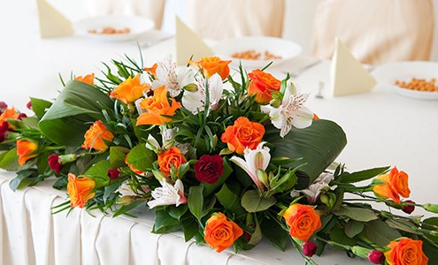 A floral centerpiece decorates a table in white, orange, and red, with foliage.