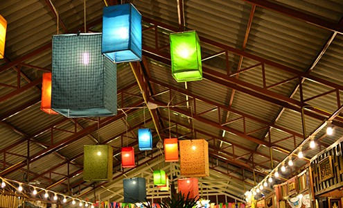 Lanterns of varying colors light up the ceiling of an event.