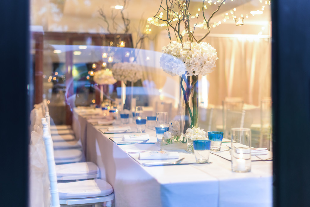 A long rectangle table set with blue decorations and white flowers.