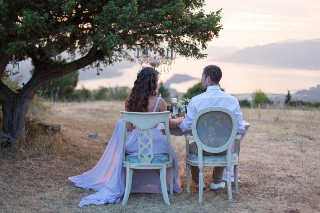 A newly wedded couple sits together under a tree.