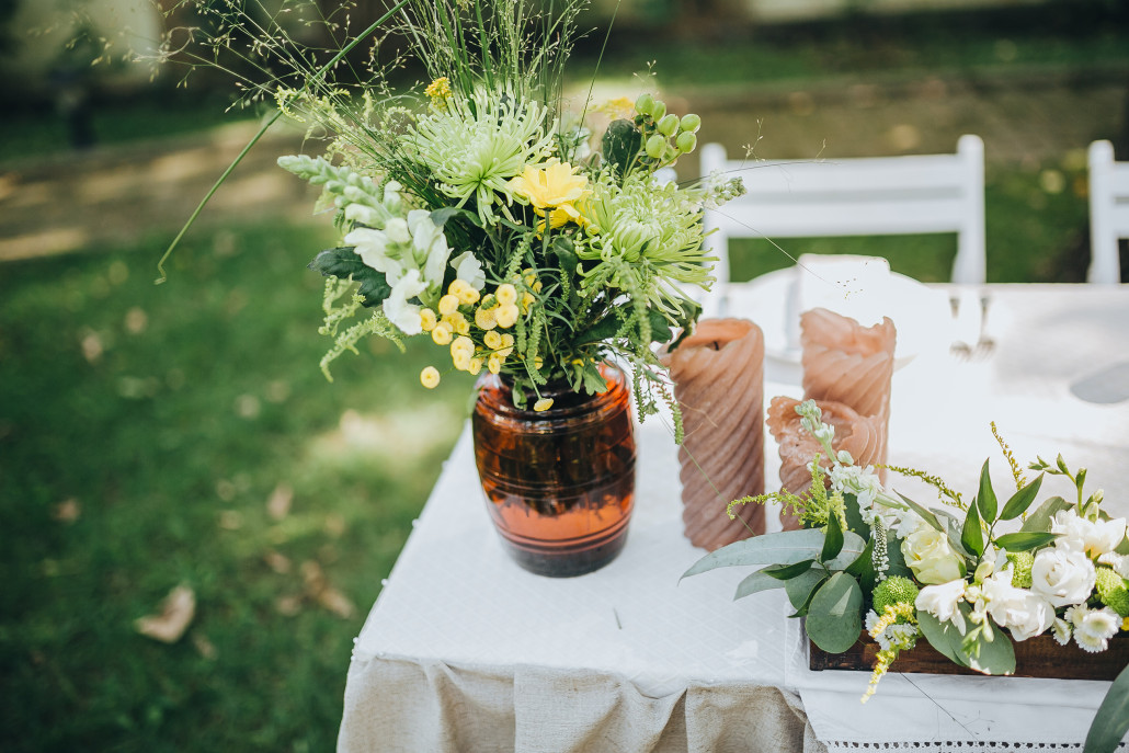An outdoor wedding table set with flowers and candles.