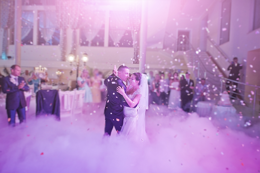 A newly wed couple dance together amidst colored smoke, confetti, and soft pink lighting.