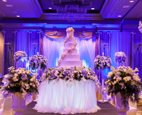 Indoor wedding reception, multi-tier white cake with floral arrangements and blue lighting.