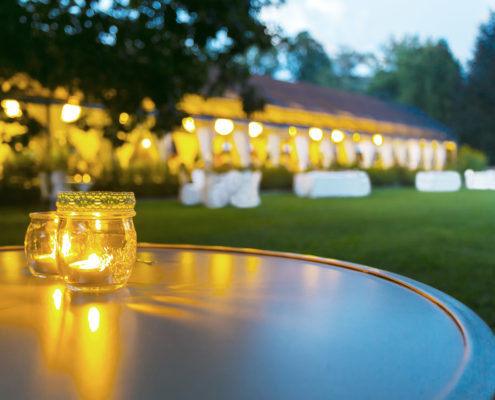 Outdoor wedding tent in evening, candlelit table