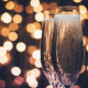 Two bubbling champagne glasses are pictured, while blurry lights in the background imply a festive setting.