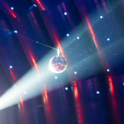 A light shines on a disco ball, with even more party lights present in the background.