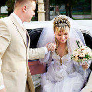 Happy bride and groom exiting limousine.